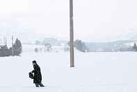 Businessman walking through snow in rural landscape, side view