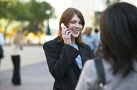 Woman using mobile phone, smiling