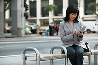 Woman sitting on bench using orgainzer