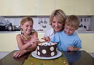 Mother decorating cake with son and daughter (6-8) in kitchen, smiling