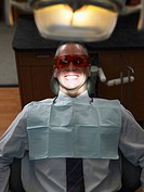 Mature man wearing protective eyewear in dentist´s chair, smiling