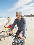 Mature couple riding bicycles on beach, smiling