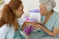 Senior woman looking at woman´s engagement ring, smiling