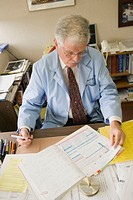 Portrait of physician in office, sitting at desk, doing paper work