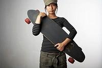 Woman holding skateboard, portrait