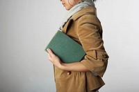 Woman holding book under arm