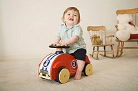 Baby boy (9-12 months) riding toy car