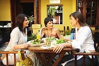 Three women having lunch in restaurant, smiling