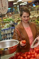 Mid adult woman buying tomatoes in a supermarket