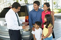 Family in car showroom talking to salesman beside SUV