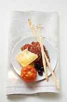 Salami, cheese, olives, tomato and grissini on plate