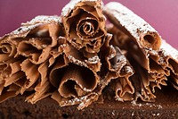 Chocolate curls with icing sugar on chocolate cake