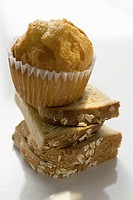 Slices of bread in a pile with a muffin on top