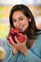 Young woman holding nectarines in her hand