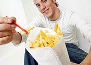 Portrait of a young man holding a fork with a French fry