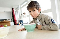 Portrait of a boy sitting at the dining table with a bowl in front of him