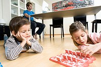 Boy and a girl lying down in front of a game with their father using a computer in the background
