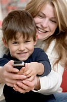 Close-up of a mother and her son using a mobile phone