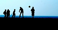 A group of children play with a ball at the beach of Scheveningen.