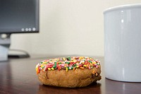 Coffee cup and doughnut on desk