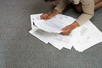 Woman looking at paperwork on floor