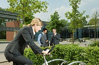 Woman on bike, two businessmen on background