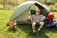 Boy sitting in front of tent