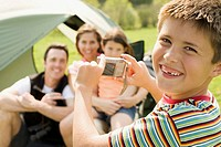 Boy taking photo of family sitting in front of tent