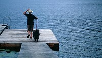 Boy (11-13) walking dog on dock, rear view, summer