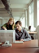 Man sitting at desk working with female colleague