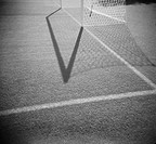 Shadow of soccer goal net on field with marking lines (grainy)