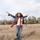 Young woman walking across field, arms outstretched, smiling