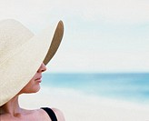 Woman wearing sun hat on beach, side view