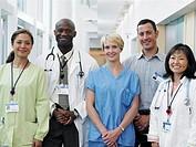 Five doctors and nurses standing in hospital corridor, portrait