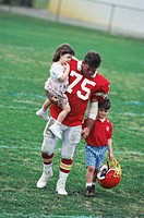 Father in football uniform walking with children (3-7)