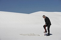 Businessman digging hole in white sand dune