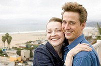 Couple on balcony overlooking ocean, smiling, close-up, portrait