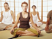Four adults sitting in lotus position, meditating, eyes closed