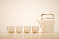Teapot next to four tea cups