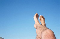 Bare footed man with legs crossed in air, low section, low angle view