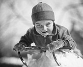 Boy (6-7) lying on sled in snow, (B&W), portrait