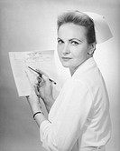 Nurse holding patient´s chart in studio, (B&W), portrait