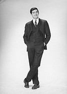 Elegant man with hands in pockets posing in studio, (B&W), portrait