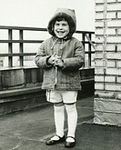 Smiling girl (8-9) wearing coat with hood, outdoors, (B&W)