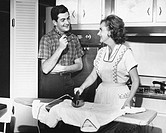 Young couple in kitchen, woman ironing, (B&W)