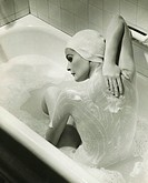 Woman washing herself in bathtub, (B&W), elevated view