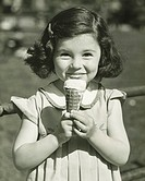 Girl (3-4) holding ice cream, posing outdoors, (B&W), portrait