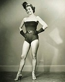 Young woman in showgirl leotards standing in empty room, (B&W)