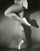 Chorus girl dancing in studio, (B&W), low section