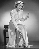 Woman applying perfume on leg, (B&W), portrait